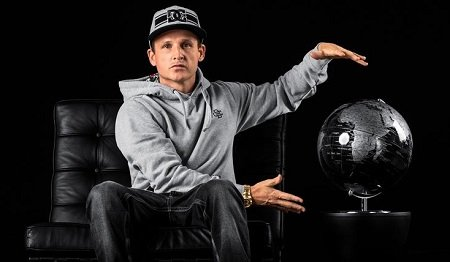 Rob Drydek showcasing a black globe while sitting on a couch with black background.