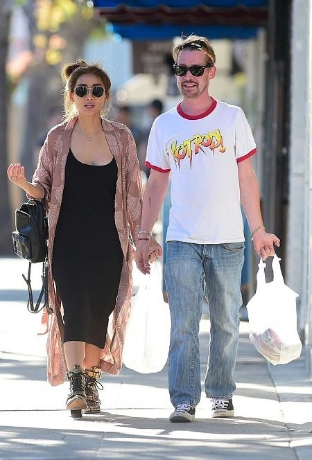 Brenda Song, net worth = $7 miillion, and Macaulay Culkin, net worth = $16 million, holding hands while walking together.