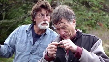 Marty Lagina (right) looking at an excavated object in his hand while Rick Lagina (left) stretches his neck to look at the object.