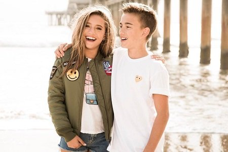 Mackenzie Ziegler and Johnny Orlando arm-in-arm smiling.