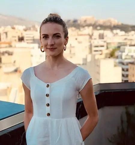 Julie Nolke in a white dress in an European city.