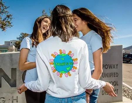 Ellie Zeiler facing backward with her twin friends in front of her.