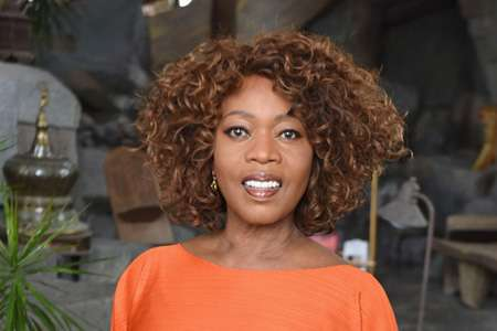 Alfre Woodard with her hair out and wearing an orange dress will appear in SEE for Apple TV+.