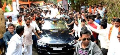 Aditya Thackeray on her car at a rally