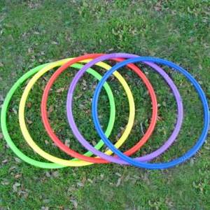 photo of five variously colored Hula Hoops laid down flat on a grassy lawn - green, yellow,orange, purple, blue