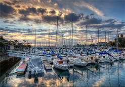 photo of moored sailboats side by side in marina slips with moody sunset sky reflected in placid water