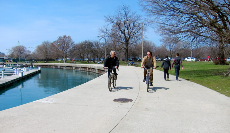 On the rim (cyclists ride along Montrose Harbor)