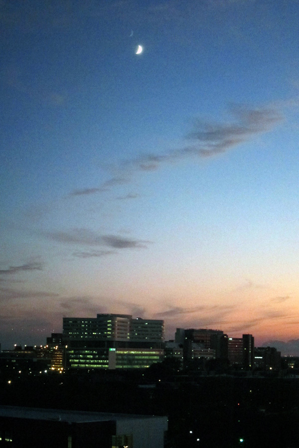 The moon in the twilight, over the new Rush hospital building on Chicago's west side.