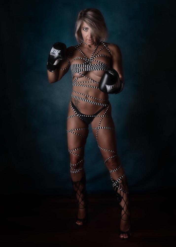 Femme en nu artistique portant des gants de boxe et une ficelle rayée blanche et noire