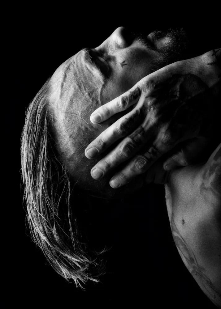 Homme rasé et tatoué en nu artistique avec une crinière de cheveux la tête en arrière