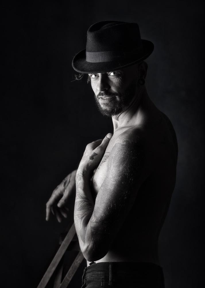 Homme tatoué en nu artistique portant un chapeau