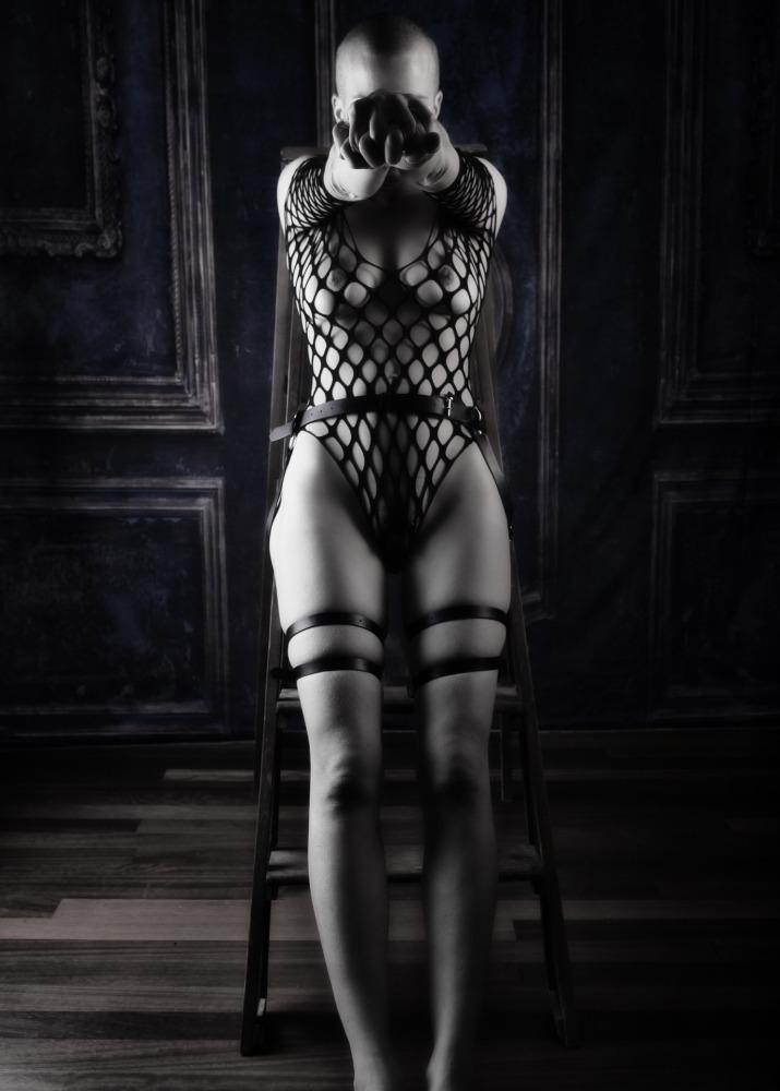 Femme au crâne rasé en nu artistique les poings serrés en clair obscur