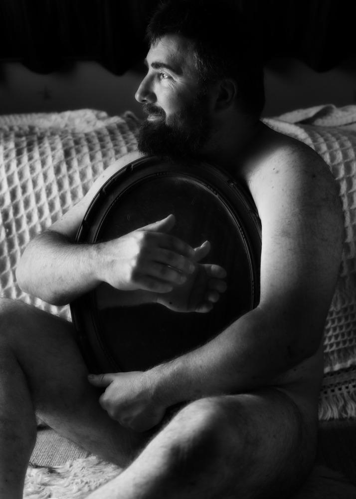 Homme barbu en nu artistique portant un miroir dans ses bras en noir et blanc