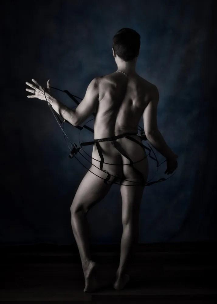 Femme debout en nu artistique et clair obscur de dos dans une crinoline noir