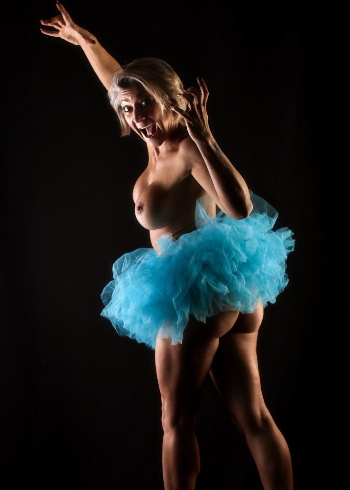 Femme quadragénaire athlétique en nu artistique portant un tutu bleu en clair obscur