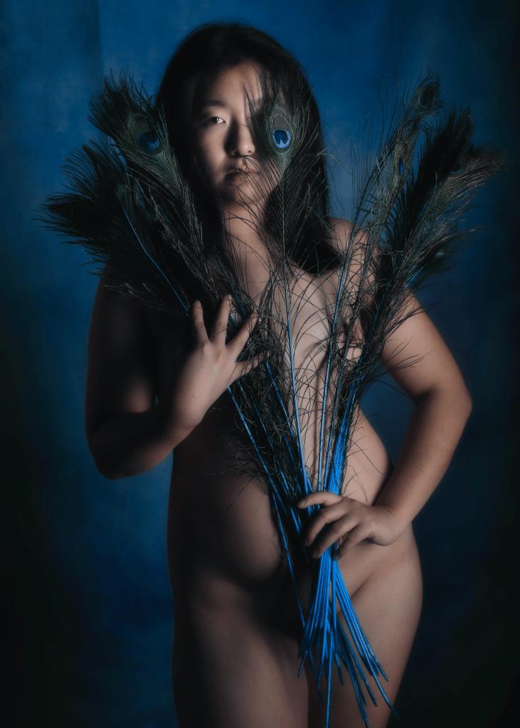 femme asiatique en nu artistique jouant avec des plumes de paon