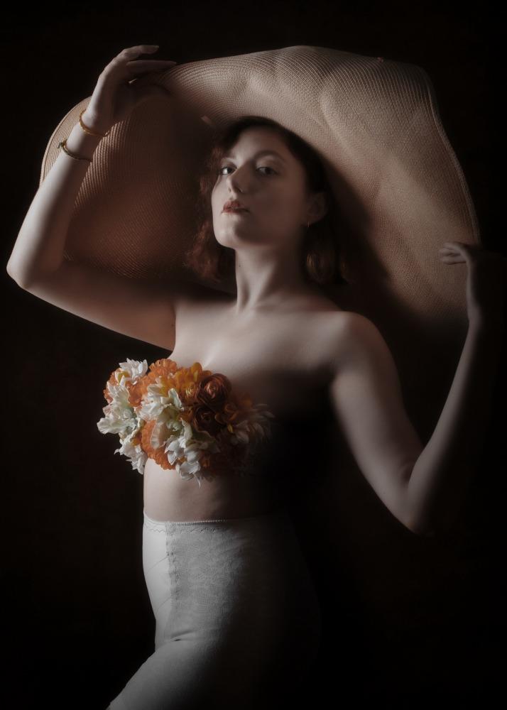 portrait en clair obscur d'une jeune femme modèle portant un grand chapeau et un soutien gorge fleuri culotte gaine ancienne