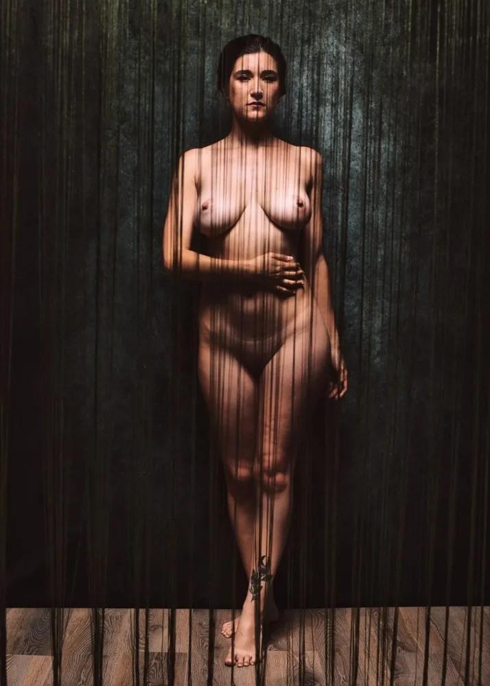 femme en nu artistique debout derrière des lignes matrix matrice