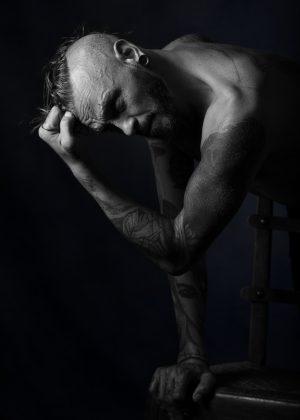 portrait d'un homme en clair obscur noir et blanc de profil la main attrapant la crinière de cheveux longs