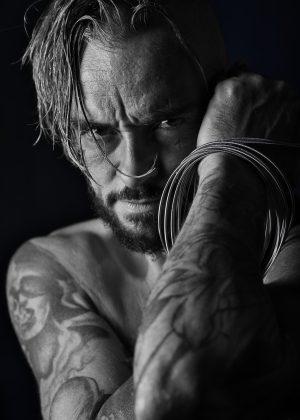portrait en noir et blanc homme tatoué en nu artistique cheveux longs et cordes de basse