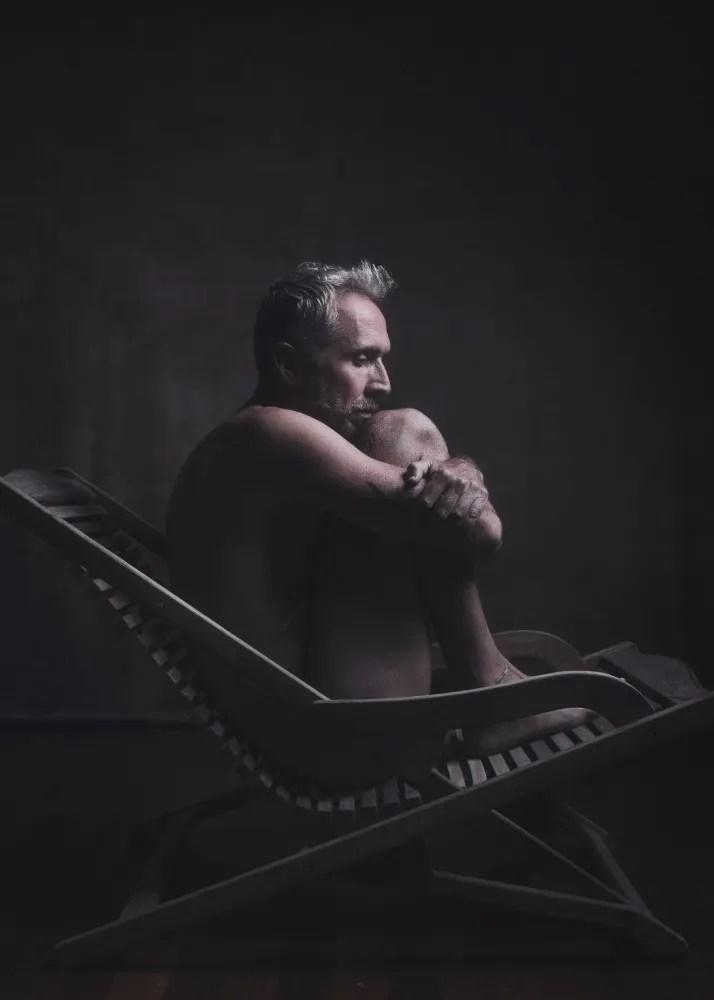 homme en nu artistique clair obscur assis sur une chaise longue en bois