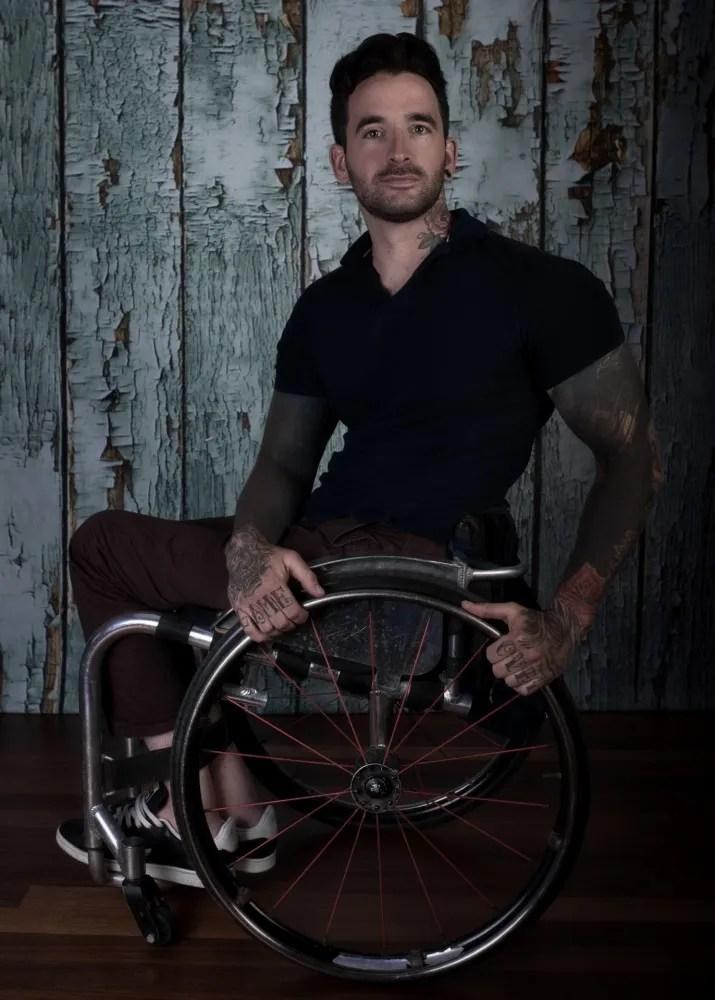 homme handicapé tatoué dans un fauteuil roulant