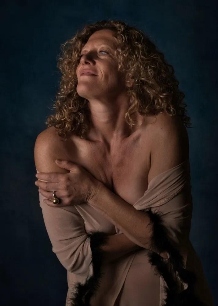 femme en nu artistique aux cheveux bouclés dorés dans un peignoir transparent couleur chair