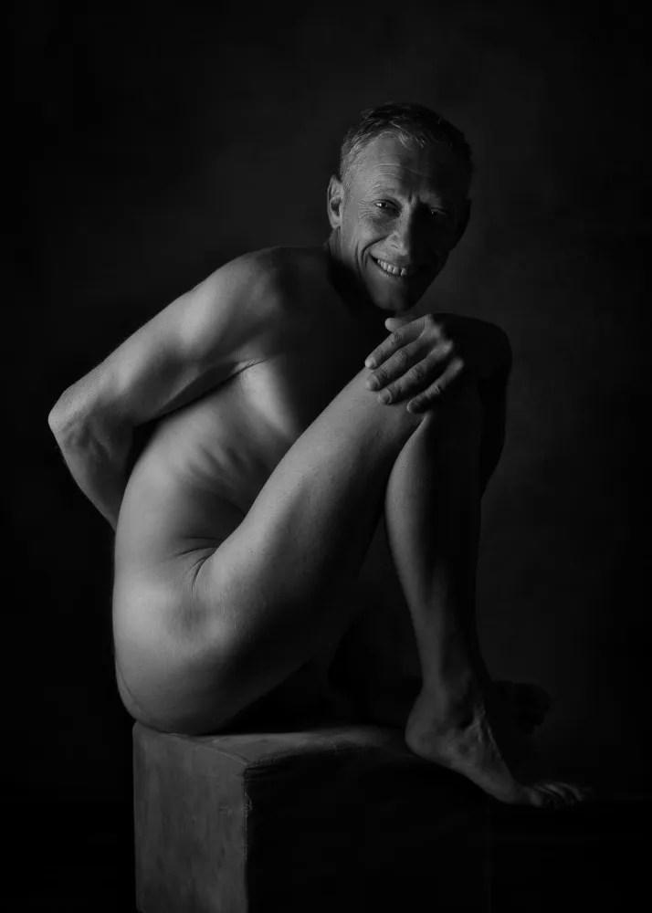 homme en nu artistique assis de profil souriant en clair obscur