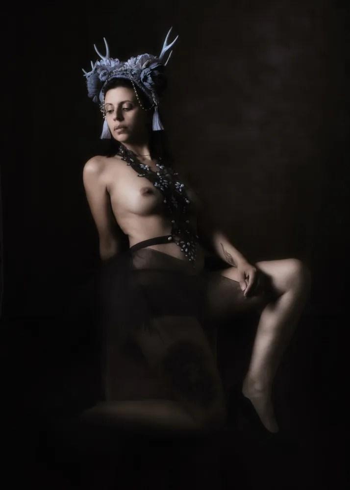 femme en nu artistique clair obscur portant une coiffe à cornes grises et un tutu noir
