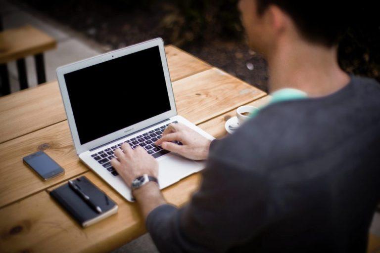 Un hombre sentado y escribiendo en su computadora