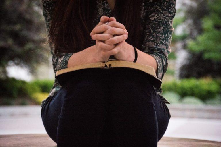 Una mujer sentada con su Biblia abierta y a la vez orando a Dios