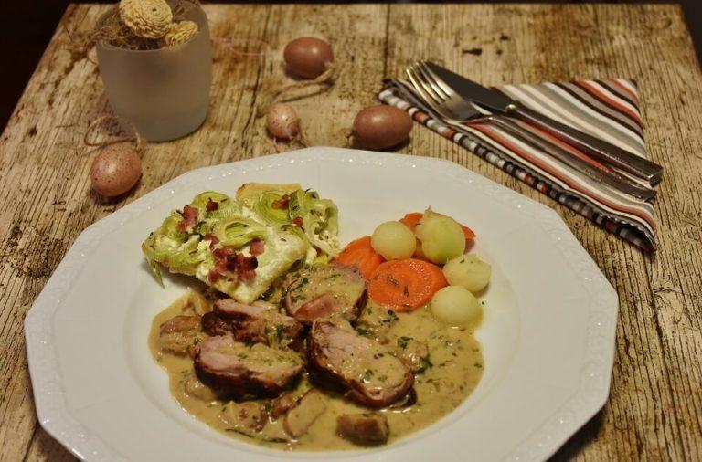 en una mesa esta un plato con pollo y verduras y enseguida estan los cubiertos y servilleta listo para comer