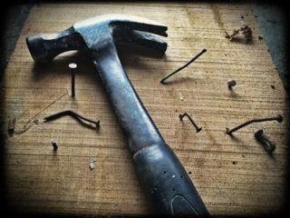 En una mesa esta el martillo con algunos clavos