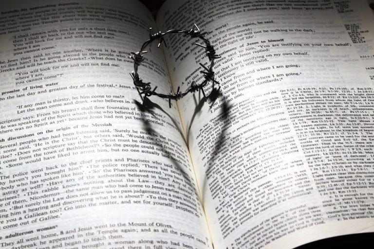 Una Biblia abierta y enmedio de las dos lados esta una corona de espinas
