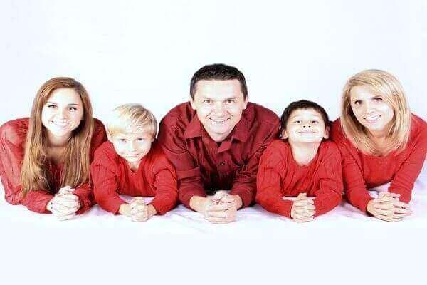 Es una foto de una familia formada por los padres una hija y dos ninos y todos estan vestidos de color rojo