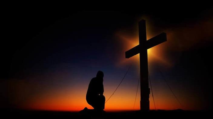 Es un hombre adorando e incado frente a una cruz