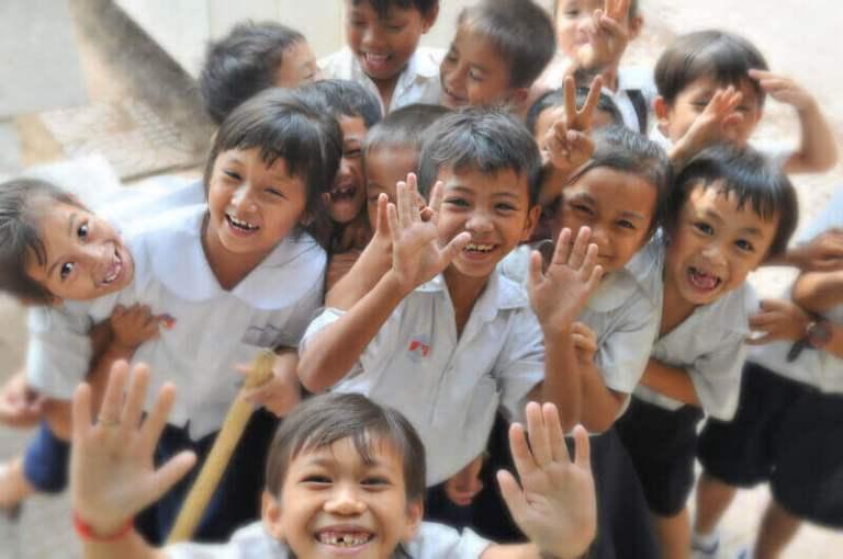Es un grupo de ninos sonriendo de una escuela posando para la foto
