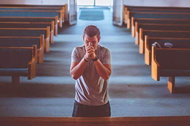 Dentro de una iglesia cristiana esta un hombre parado en el altar arrepintiendose de sus pecados