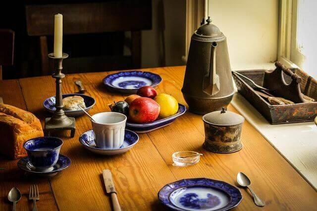 Es una mesa y arriba tiene la cafetera tasas para el cafe y unas frutas