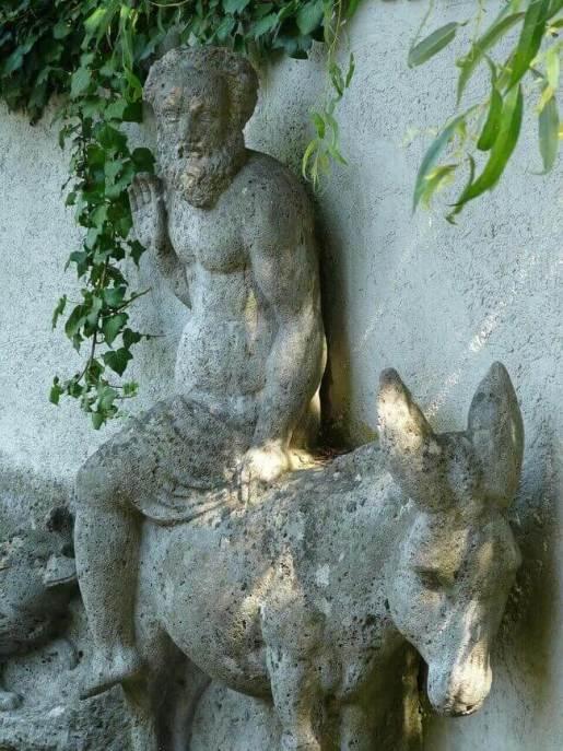 Es una figura de piedra de un asna y una persona arriba estan cerca de una pared