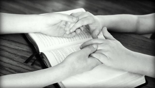 Son cuatro manos dos son del padre y las del hijo y estan puestas sobre la Biblia abierta