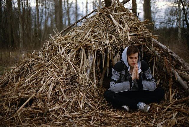 Es un joven orando en el bosque