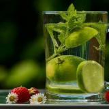 Es un vaso de agua con rodajas de limon y hojas de menta