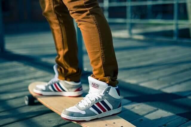 Es un skateborder y un joven arriba solo que se ven solo los pies de un joven