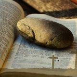Es una Biblia abierta que tiene tres cruces y una piedra