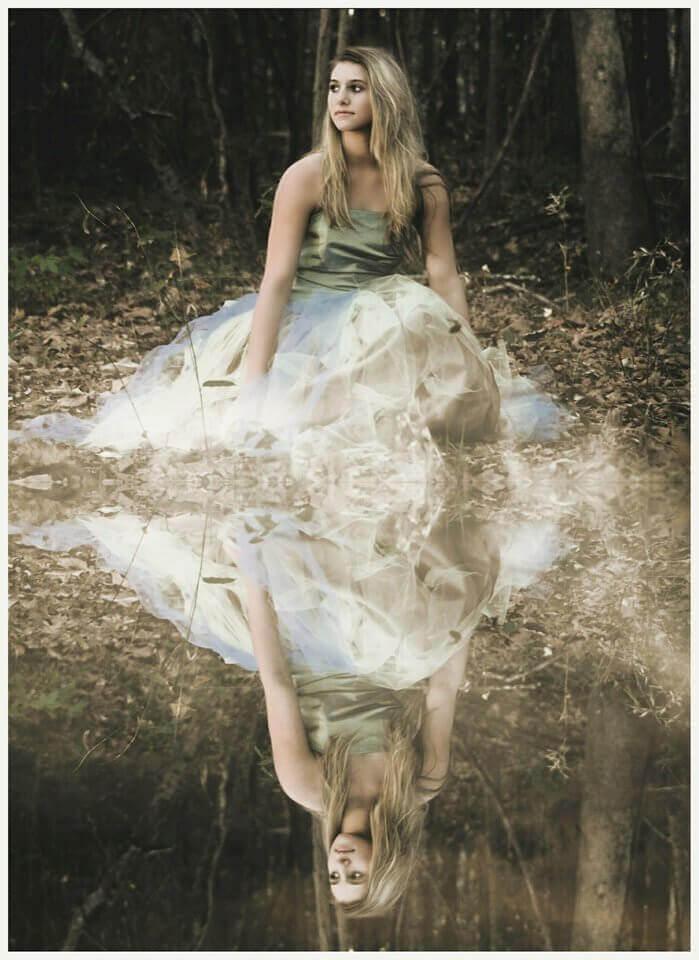 Es una joven muy linda cerca de la orilla de un lago donde se refleja su imagen en el agua