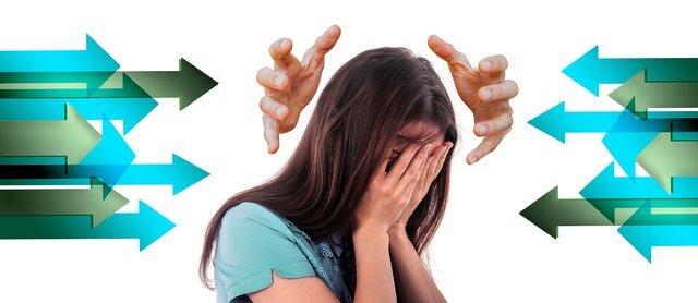 Es una mujer con su cara tapada con sus manos agligida y 2 manos que quieren tocar su cabez