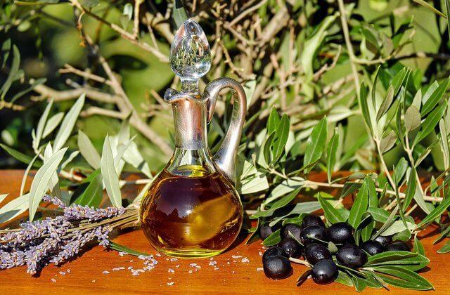 Es una botella de aceite con unas aceitunas negras y unas ramas de olivo