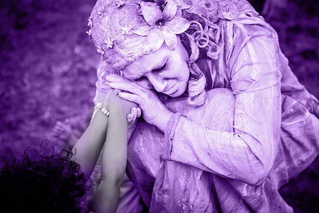 Es una estatua de una madre acariciando las manos de una joven
