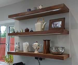 Floating shelves in walnut with inset LED lighting by Celtica Kitchens